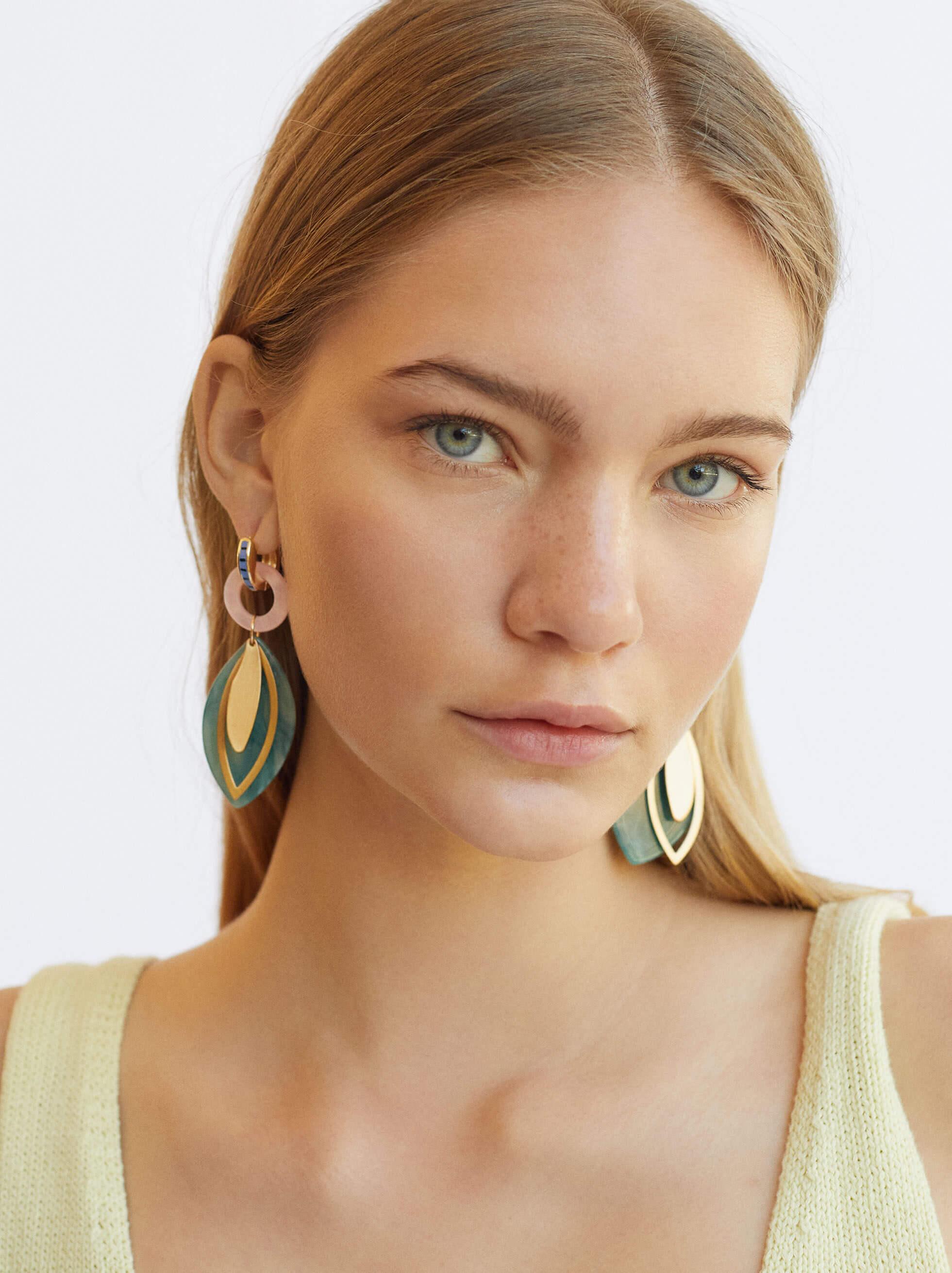 mulher loira de olhos verdes a usar brincos da parfois