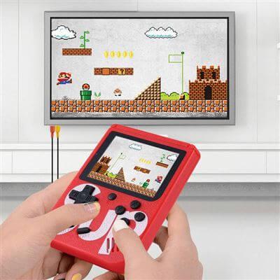 """Mini Consola Retro Portátil vermelha com Ecrã 3"""" a transmitir para uma televisão montada numa parede branca"""