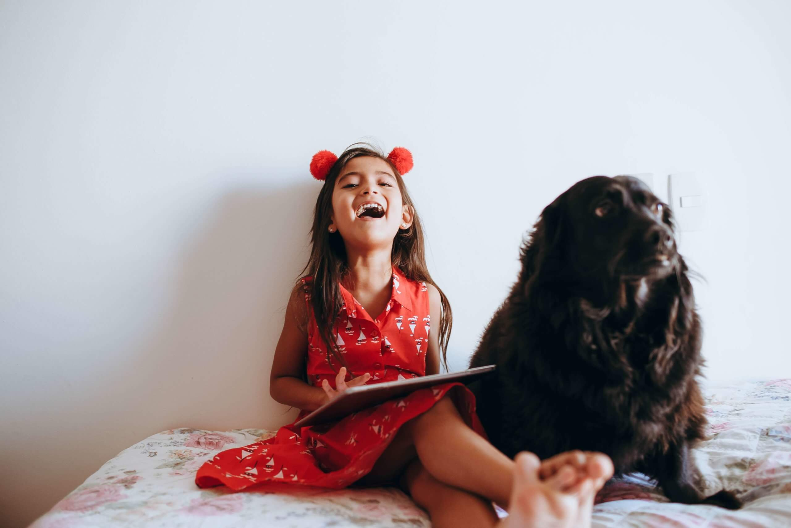 criança menina sentada na cama com livro no colo, a rir-se e com um cão sentado ao lado dela