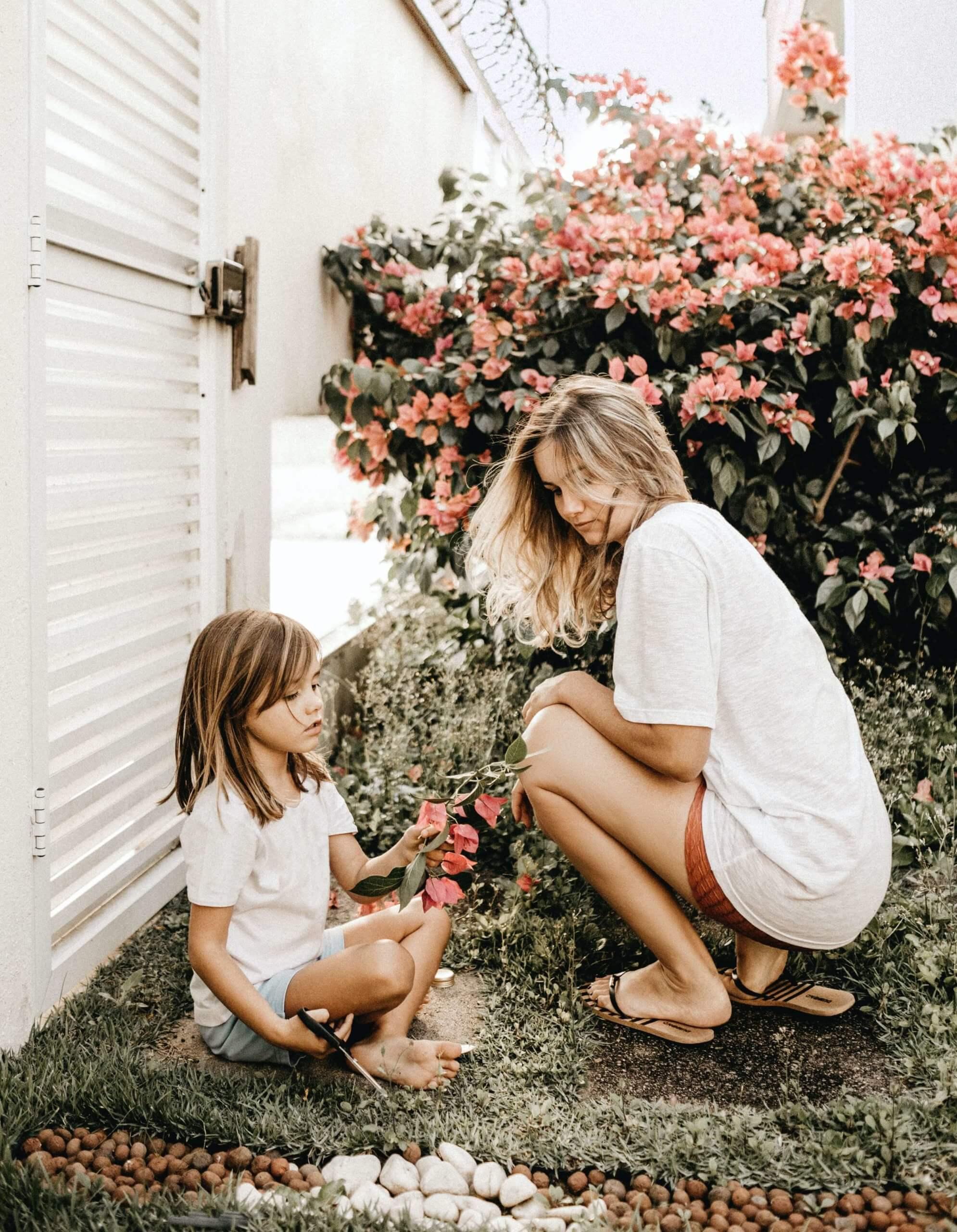 mãe e filha a colher flores