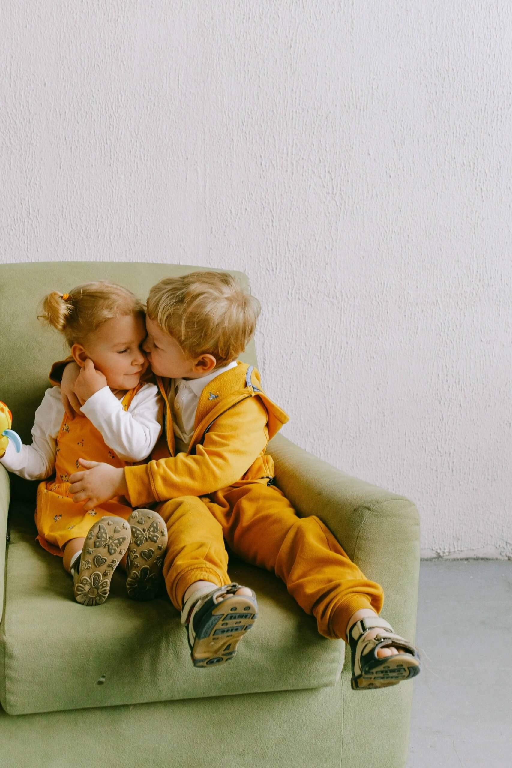 menino a dar um beijinho a menina sentados num sofá verde