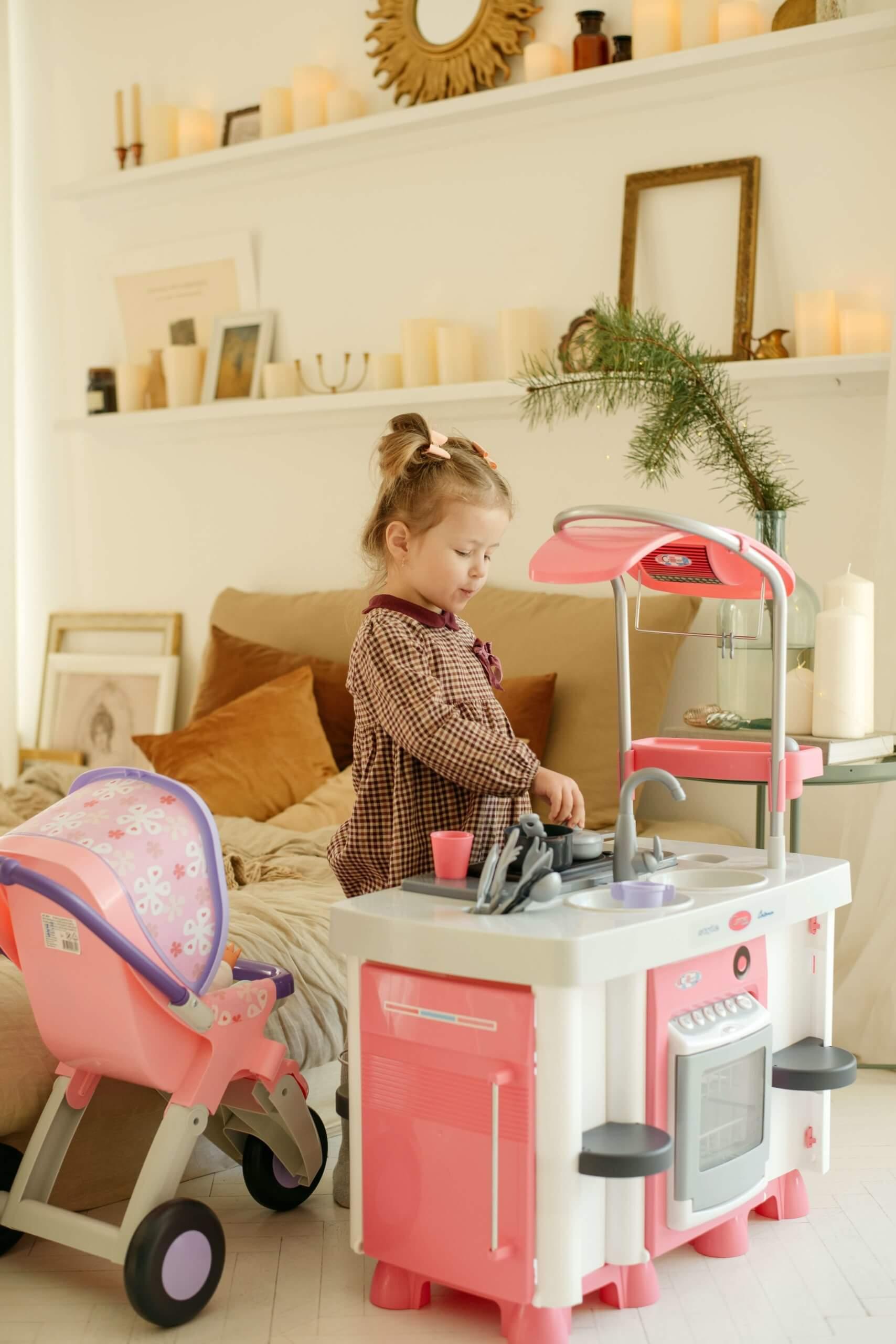 menina a brincar com cozinha de brincar