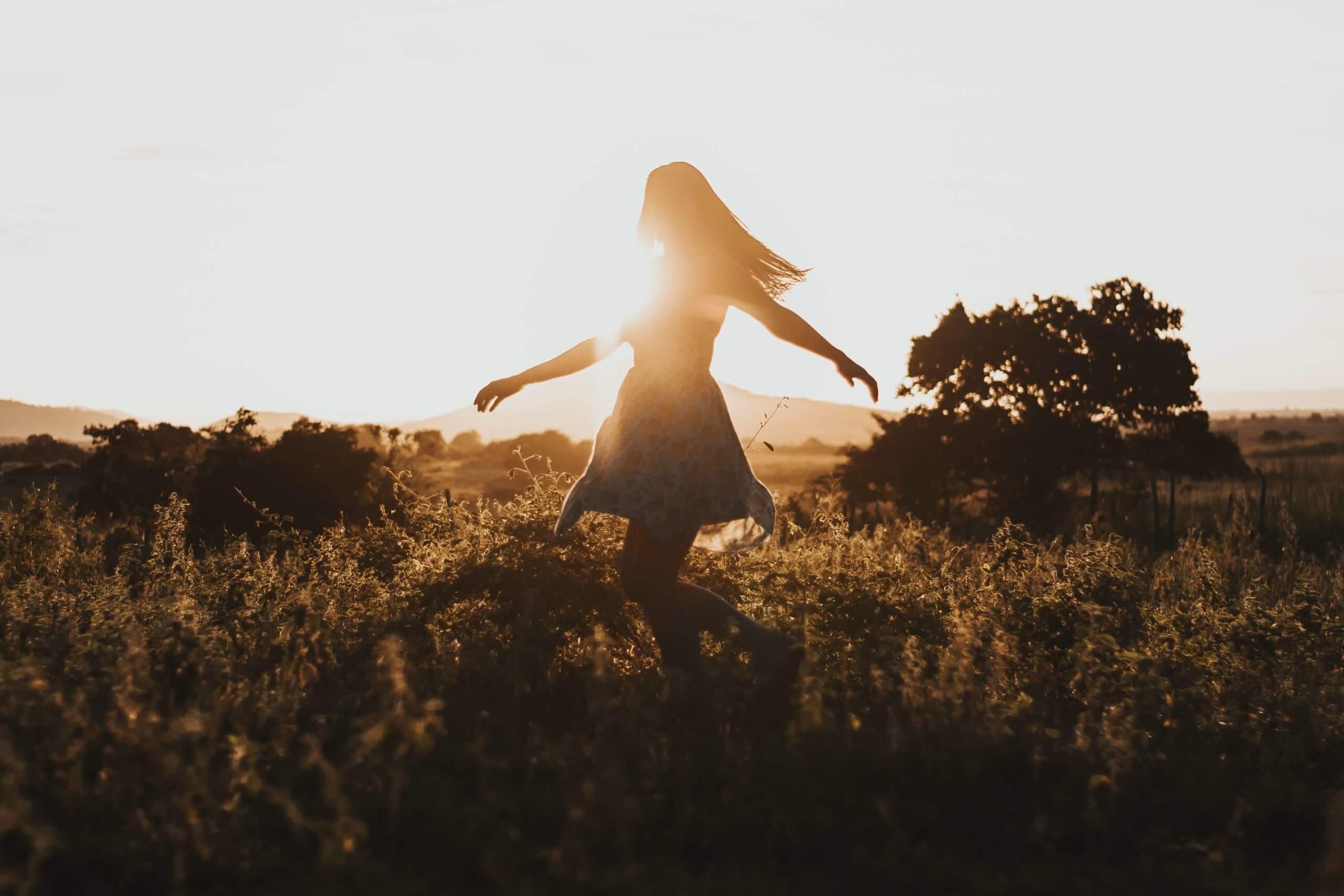 mulher a dançar na natureza ao por do sol