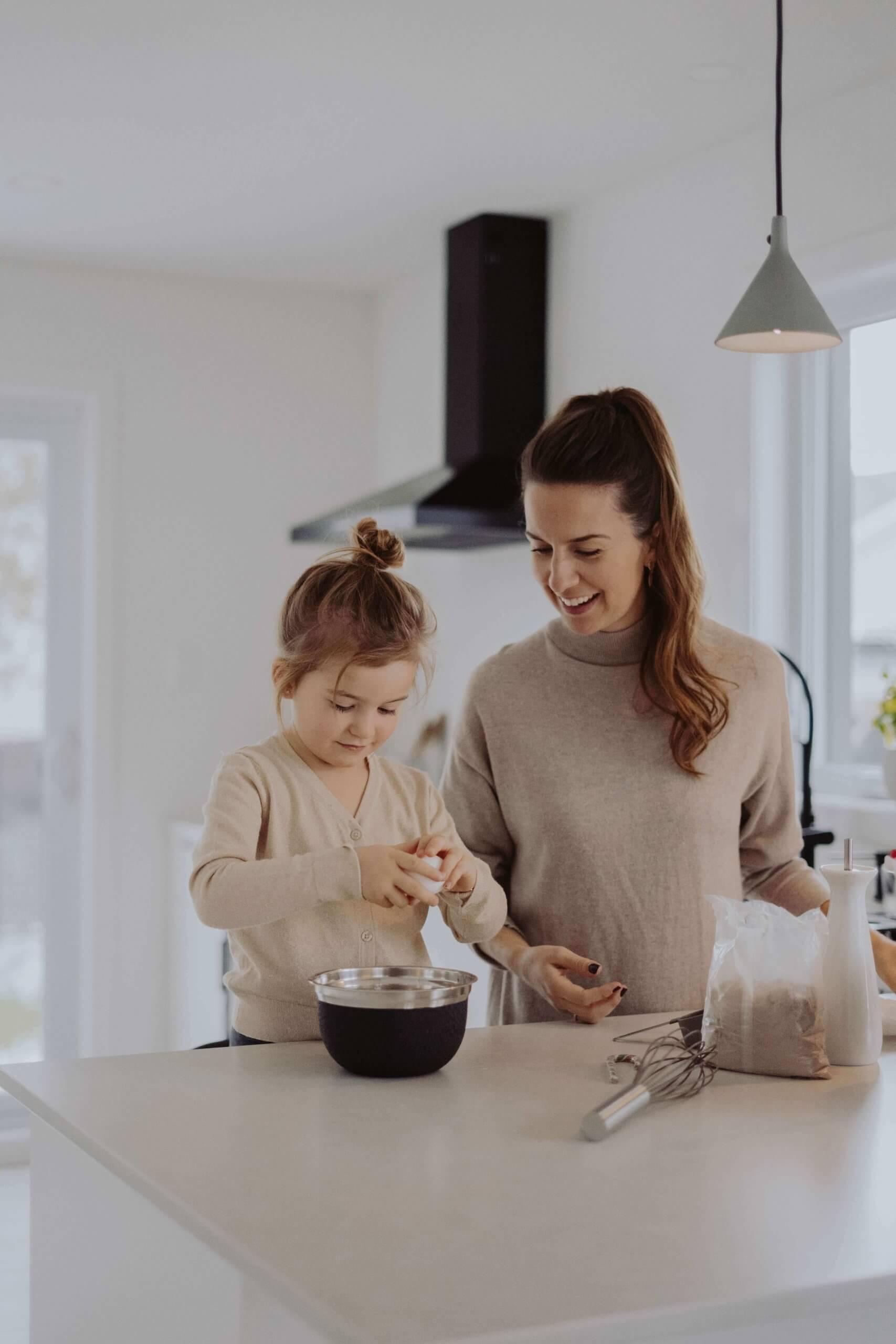 mão e filha a confecionar um bolo na cozinha