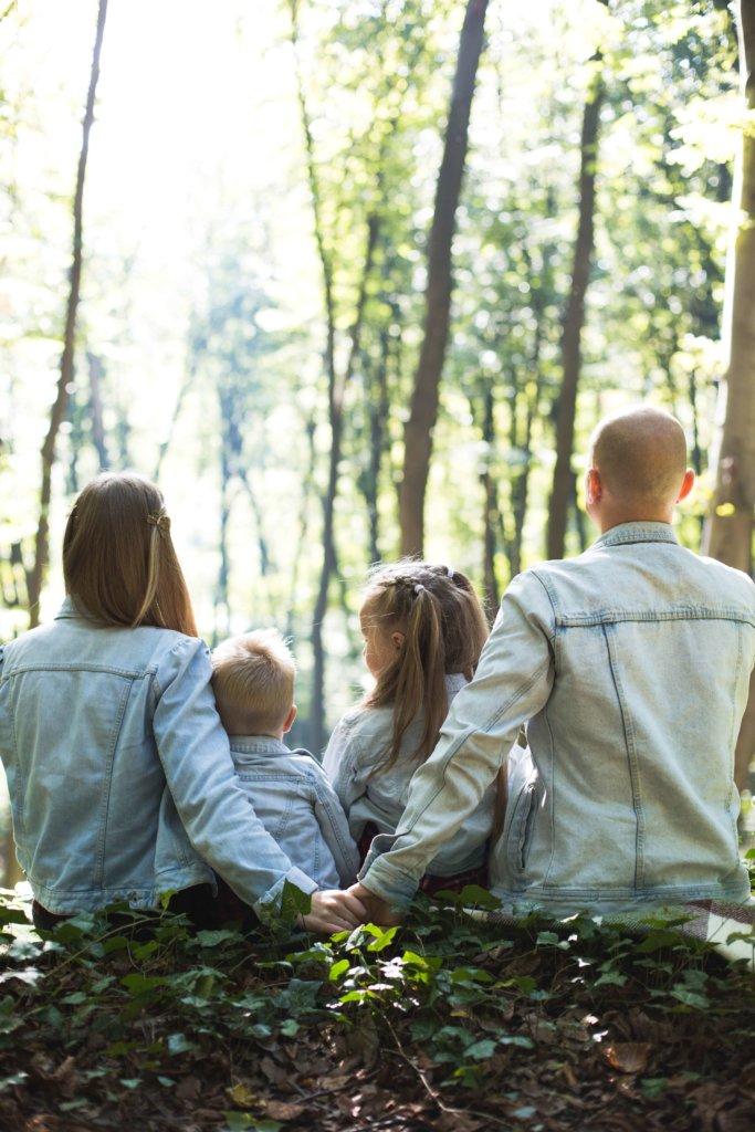 família sentada na floresta