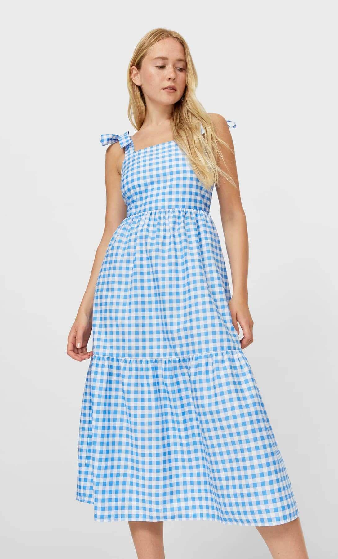 mulher com vestido branco com padrão de quadrados azuis da Stradivarius