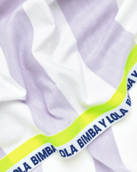 toalha de praia às riscas brancas e lilás da bimba y Lola